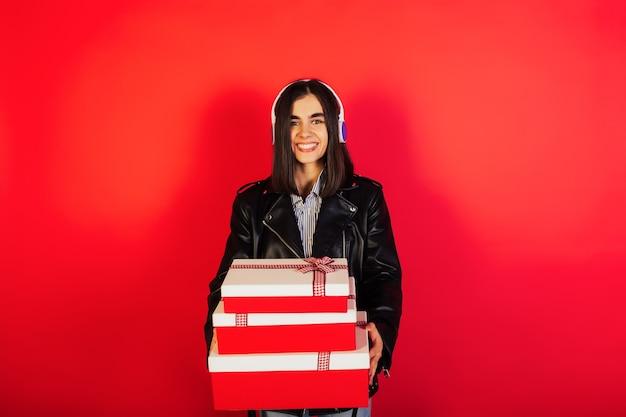 Jonge vrouw luistert naar muziek met een koptelefoon en houdt drie geschenkdoos op rode muur