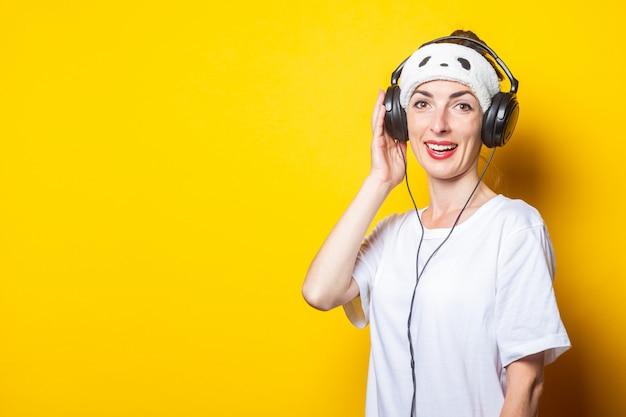 Jonge vrouw luistert naar muziek op koptelefoon.