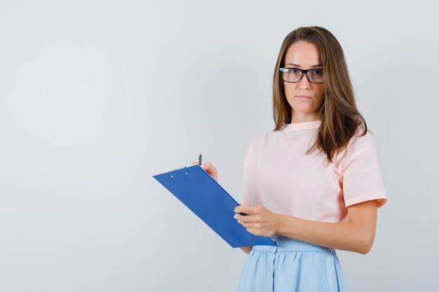 Jonge vrouw maakt aantekeningen op klembord in t-shirt, rok, vooraanzicht.