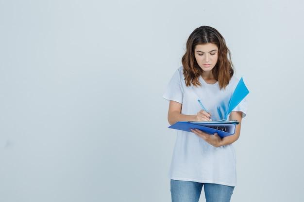 Jonge vrouw maakt aantekeningen over mappen in wit t-shirt, spijkerbroek en zoekt druk, vooraanzicht.
