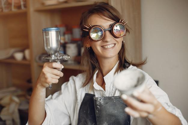 Jonge vrouw maakt aardewerk in werkplaats