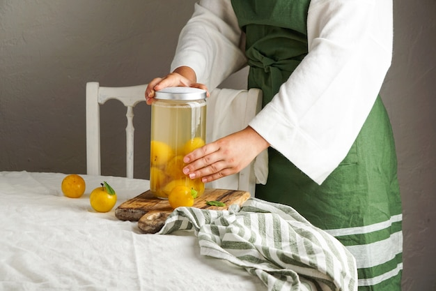 Jonge vrouw maakt compote van gele pruimen. conservering in een glazen pot. voorbereidingen voor de winter, voor toekomstig gebruik