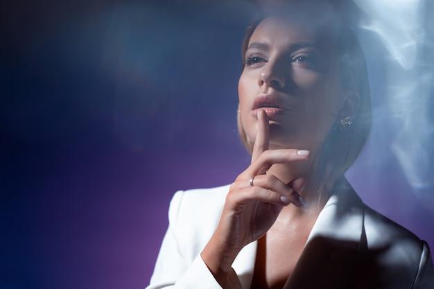 Jonge vrouw maakt een gebaar van stilte stijlvolle modieuze jonge vrouw Premium Foto
