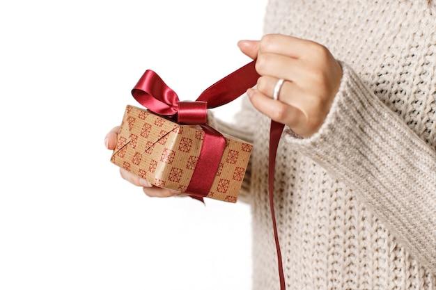 Jonge vrouw maakt een geschenkdoos los die op wit wordt geïsoleerd dicht omhoog