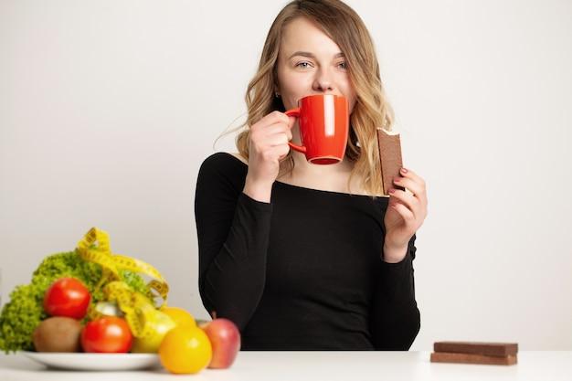 Jonge vrouw maakt een keuze tussen gezonde en ongezonde voeding.