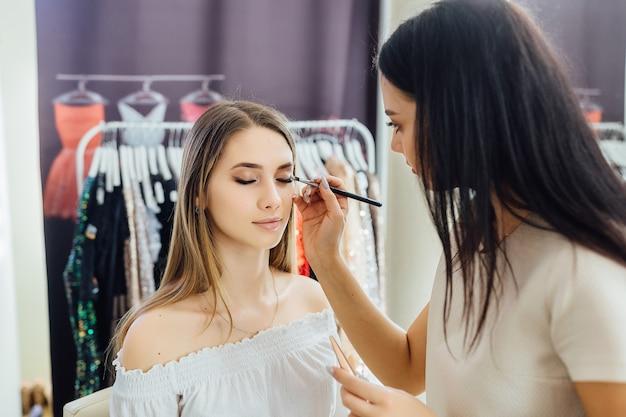 Jonge vrouw maakt een natuurlijke make-up voor een model