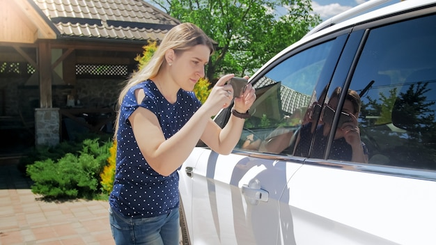 Jonge vrouw maakt foto's van haar auto op smartphone voor verzekeringsmaatschappij na auto-ongeluk.