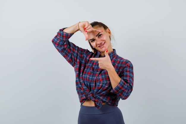 Jonge vrouw maakt framegebaar in geruit overhemd, broek en ziet er schattig uit, vooraanzicht.
