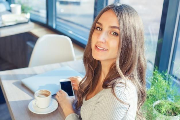Jonge vrouw maakt gebruik van een laptop en mobiele telefoon in een café