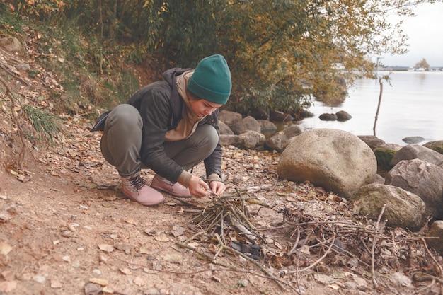 Jonge vrouw maakt open haard op het strand
