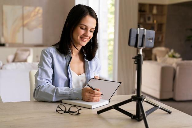 Jonge vrouw maakt thuis een vlog met haar telefoon