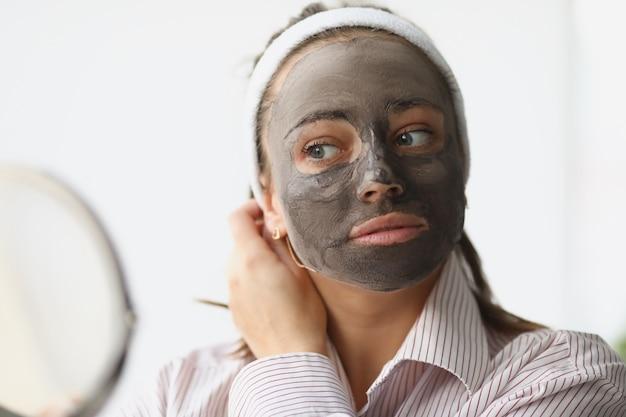 Jonge vrouw maakt verjongend gezichtsmasker van klei
