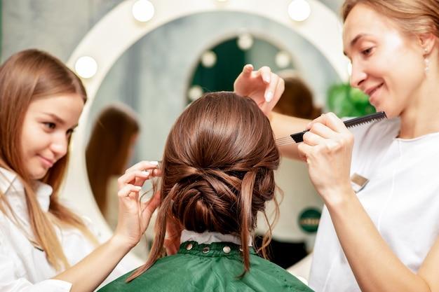 Jonge vrouw make-up en kapsel ontvangen door professionele make-up artist en kapper in de schoonheidssalon.