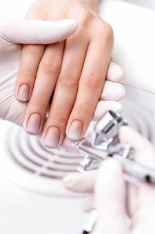 Jonge vrouw manicure ontvangen door airbrush in nagelsalon. procedure voor het spuiten van verf op de nagels