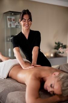 Jonge vrouw masseert haar cliënt in haar salon