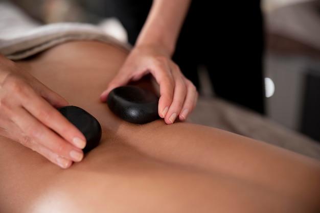 Jonge vrouw masseert haar cliënt met stenen