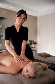 Jonge vrouw masseert haar cliënt