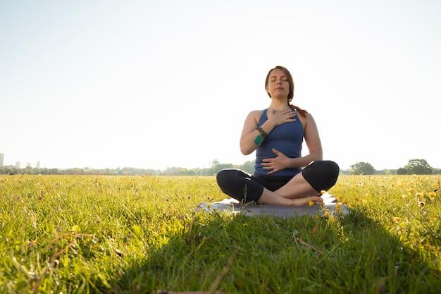 Jonge vrouw mediteert buiten op yogamat