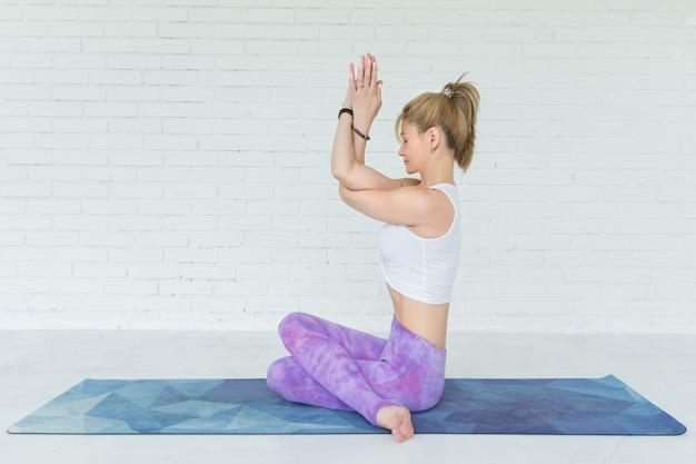 Jonge vrouw mediteert tijdens het beoefenen van yoga