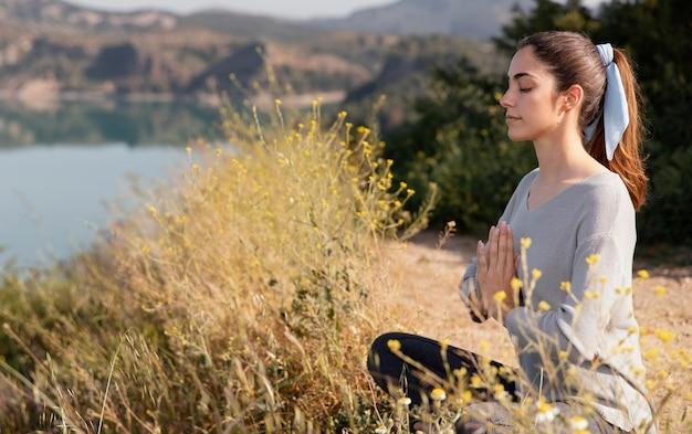 Jonge vrouw mediteren in de natuur Gratis Foto