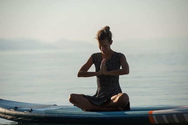 Jonge vrouw mediteren in de ochtend