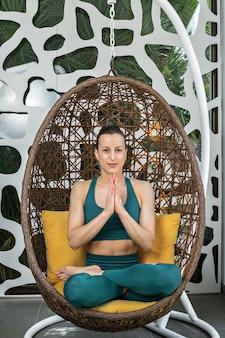 Jonge vrouw mediteren in hangende stoel