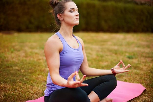 Jonge vrouw mediteren in het park. meditatie zorgt ervoor dat ik me ontspannen voel