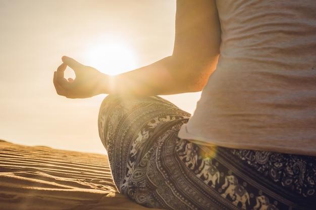 Jonge vrouw mediteren in rad zandwoestijn bij zonsondergang of dageraad