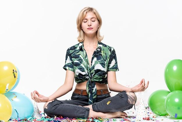 Jonge vrouw mediteren omringd door ballonnen