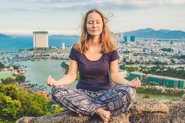 Jonge vrouw mediteren over het landschap van de oude stad op zonsopgang