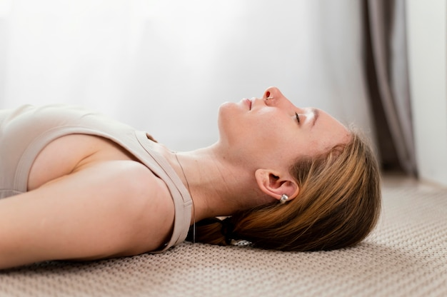 Jonge vrouw mediteren thuis gelegd op de vloer