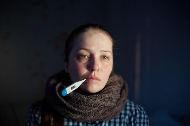 Jonge vrouw meet de temperatuur met een elektronische thermometer.