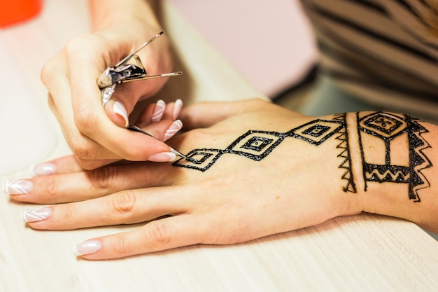 Jonge vrouw mehendi kunstenaar henna schilderen op de hand.