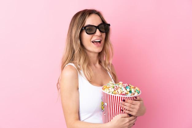 Jonge vrouw met 3d glazen en holding een grote emmer popcorns