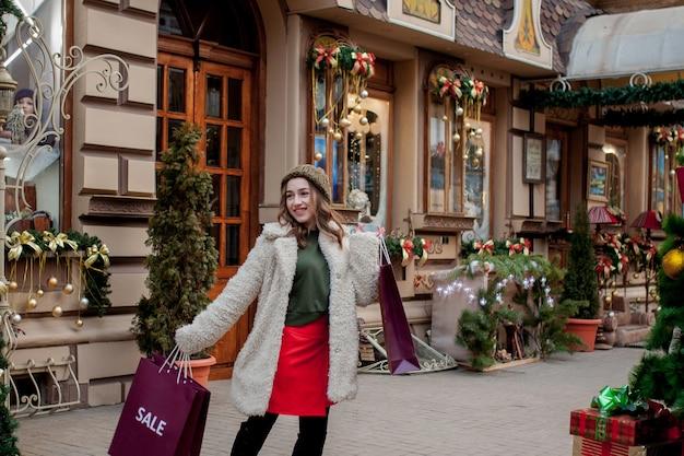 Jonge vrouw met aankopen in nieuwe jaarwinkel. kerstuitverkoop, zwarte vrijdag.