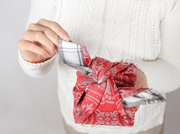 Jonge vrouw met aanwezig. furoshiki milieuvriendelijk geschenk verpakt in stof