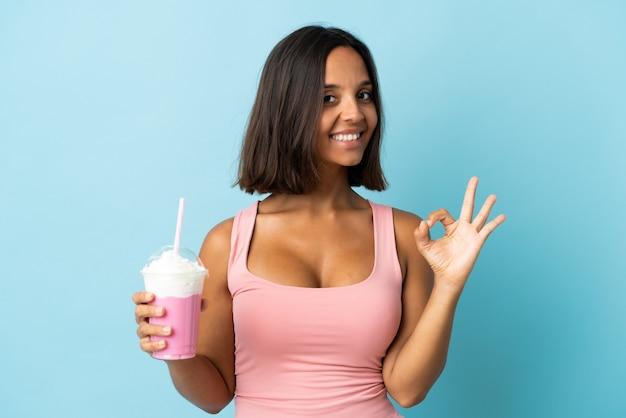 Jonge vrouw met aardbeimilkshake die op blauwe achtergrond wordt geïsoleerd die ok teken met vingers toont