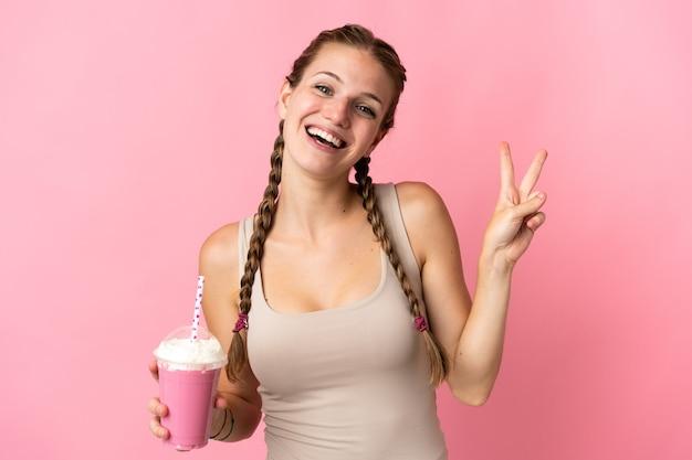 Jonge vrouw met aardbeimilkshake die op roze achtergrond wordt geïsoleerd die en overwinningsteken glimlacht toont