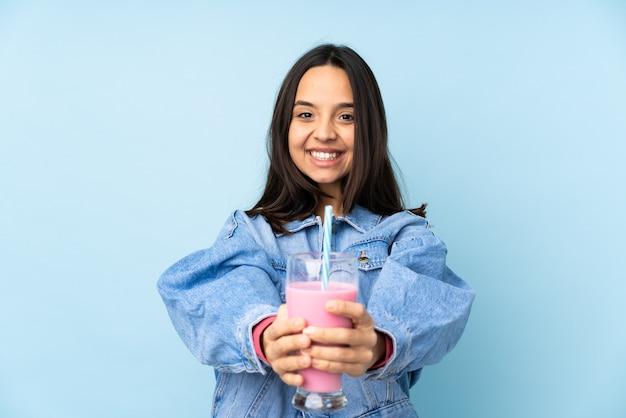 Jonge vrouw met aardbeimilkshake over geïsoleerde blauwe achtergrond die copyspace denkbeeldig op de palm houdt om een advertentie in te voegen
