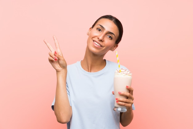 Jonge vrouw met aardbeimilkshake over geïsoleerde roze muur die en overwinningsteken glimlachen tonen
