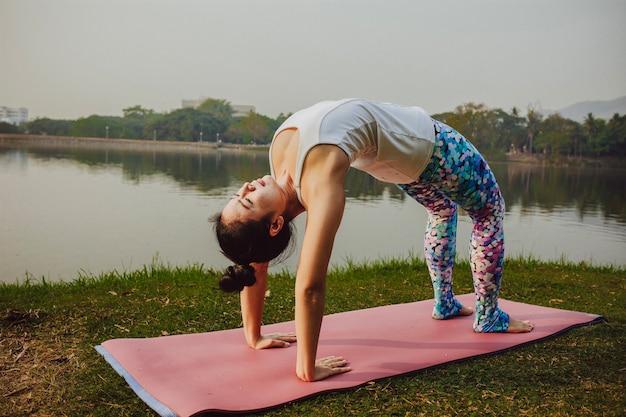 Jonge vrouw met acrobatische houding naast het meer