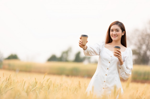 Jonge vrouw met afhaalmaaltijden koffiekopje staande buitenshuis op gerst veld land in de ochtend. gelukkige tijd.