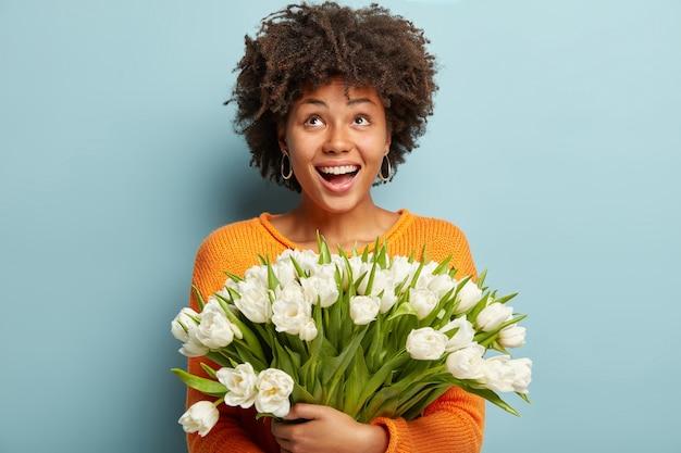 Jonge vrouw met afro kapsel bedrijf boeket witte bloemen