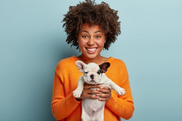 Jonge vrouw met afro kapsel bedrijf puppy