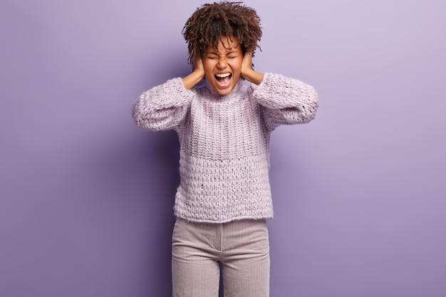 Jonge vrouw met afro-kapsel die paarse trui draagt