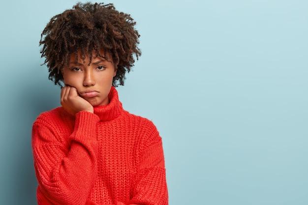 Jonge vrouw met afro-kapsel, gekleed in rode trui