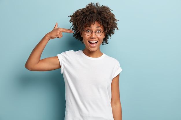 Jonge vrouw met afro-kapsel, gekleed in wit t-shirt