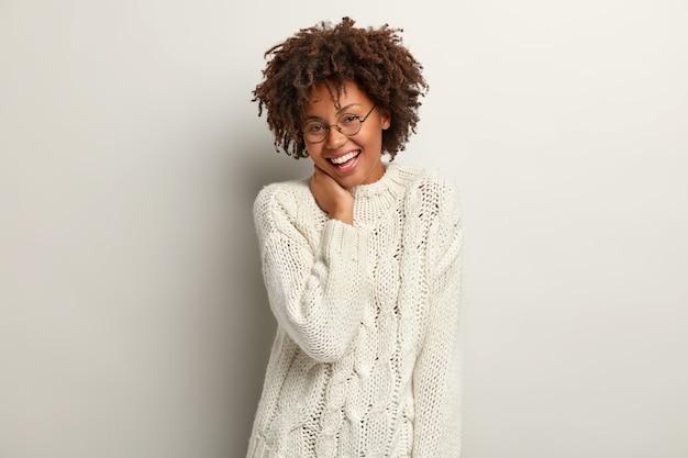 Jonge vrouw met afro-kapsel, gekleed in witte trui