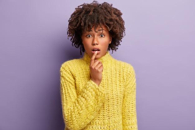 Jonge vrouw met afro kapsel gele trui dragen
