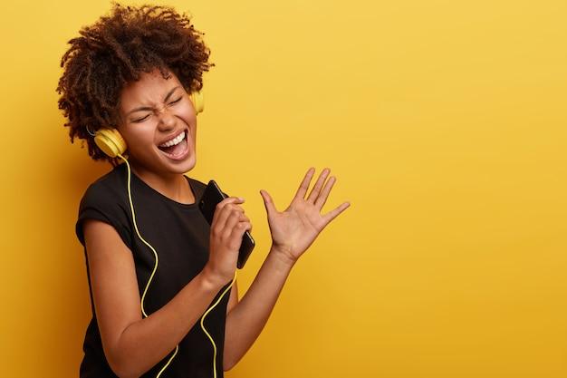 Jonge vrouw met afro-kapsel met gele koptelefoon
